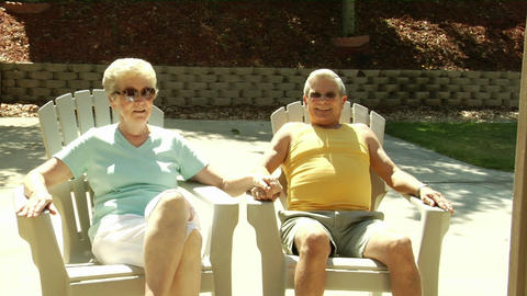 A husband and wife sit in lawn chairs holding hands Stock Video Footage