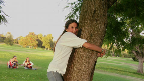 A woman in a park runs to a tree and hugs it Stock Video Footage