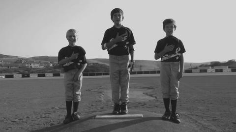 Young baseball players cover their hearts with their hats Stock Video Footage