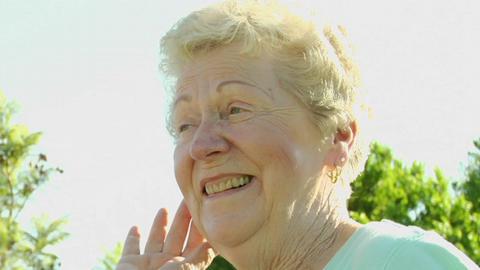 An elderly woman fluffs her hair Stock Video Footage