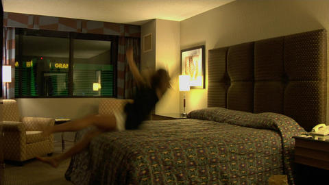 A young woman jumps backwards onto a hotel room bed Stock Video Footage