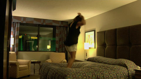 A young woman jumps on a hotel room bed Footage