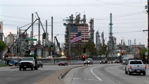 Traffic passes by an industrial plant adorned with two... Stock Video Footage