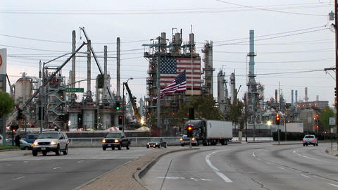 Traffic passes by an industrial plant adorned with two large American flags Footage