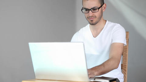 A young man sits and smiles as he starts using his laptop... Stock Video Footage
