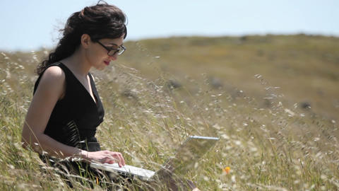 A woman using a laptop sits in a field Stock Video Footage
