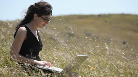 A woman using a laptop sits in a field Footage