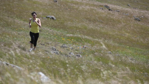 A woman jogs up the rough terrain of a hill Stock Video Footage