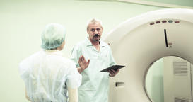 Doctor calms female patient before CT MRI scanning 4k video. Medical equipment Footage