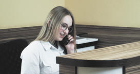 Hospital reception 4k video. Woman nurse receptionist at desk talking on phone Footage