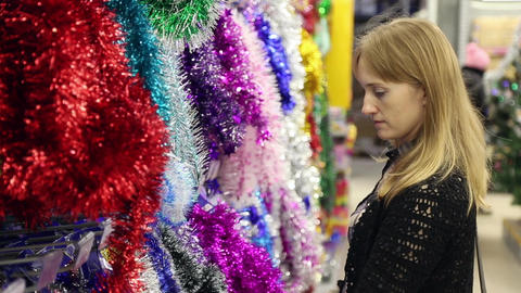 The girl chooses christmas decorations Footage