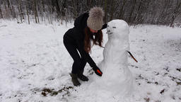Jocose woman finish snowman, put carrot lower than needed Footage