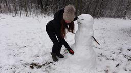 Jocose woman finish snowman, put carrot lower than needed Footage