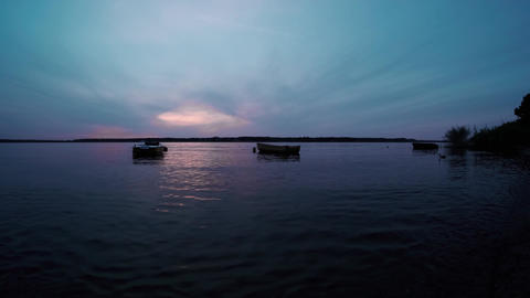 fishing boats sway slowly on the surface of the river at sunset at blue hour. Twilight on the river Live Action
