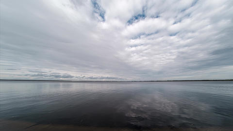 Time lapse of low-flying white and fluffy clouds over the calm water surface Live Action