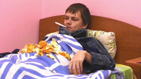 A sick man lying in bed, measuring the temperature and eats tangerines Footage