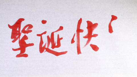 "Writing Chinese character of ""Merry Christmas"" with brush and ink on a piece of  Footage"