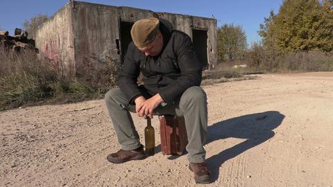 Depressed man with wine bottle sitting on suitcase Footage