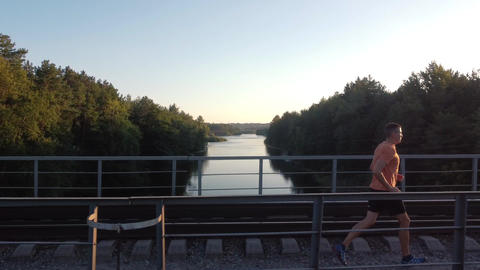 A man running on a railway bridge In Forest At Sunset. Healthy Lifestyle Concept Live Action