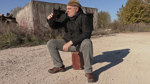 Drunk man with empty wine bottle sitting on the suitcase Live Action