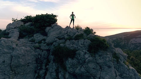Aerial - Fit woman raising arms victoriously after climbing the seaside mountain Live Action