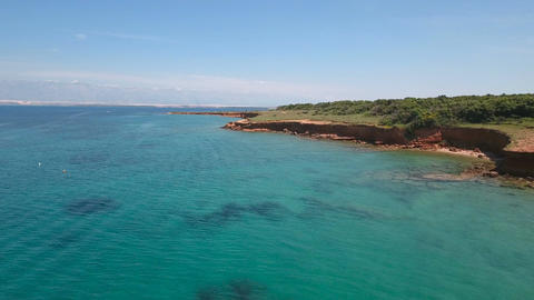 Aerial - Flying low above turquoise sea water near the coast of red earth Footage