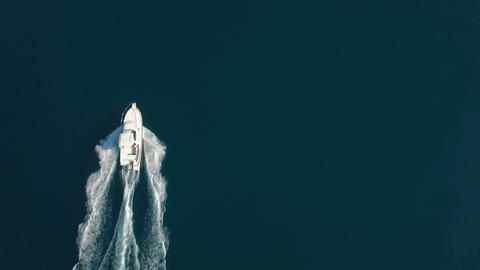 Aerial - Top down view of luxury speed boat cruising on water Footage