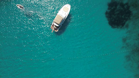 Aerial - Top down view of a person leaving the yacht with a dinghy Live Action