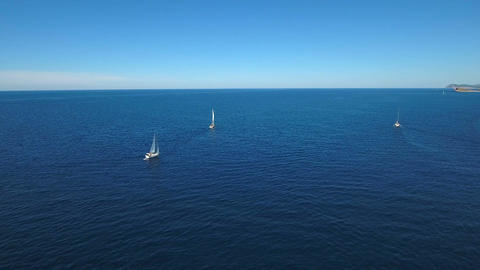 Aerial - Distant shot of a sail boats sailing on deep blue water in the Adriatic Live Action