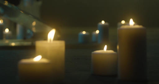 A lot of burning candles on the floor. Candles burning in the dark, glass candle Live Action