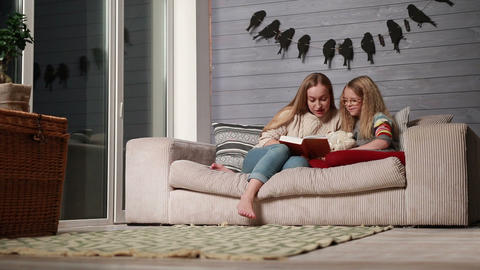Young mother reading a book to her cute daughter Footage