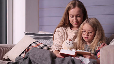 Mother and daughter reading bedtime story on sofa Footage