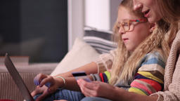 Mother and daughter shopping online together Footage