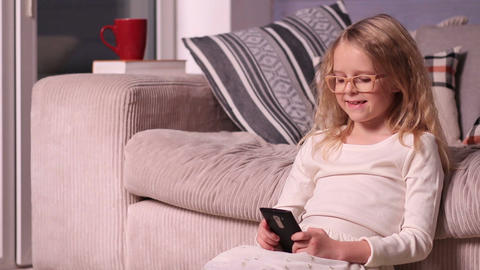 Beautiful little girl playing with smartphone Footage