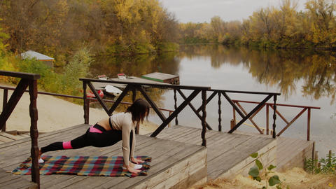 Woman doing yoga in the morning by the river, healthy woman practicing yoga, a Live Action