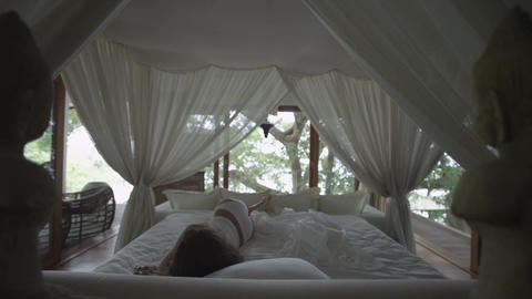 Sleeping girl wakes up. Romantic bed under the canopy.... Stock Video Footage
