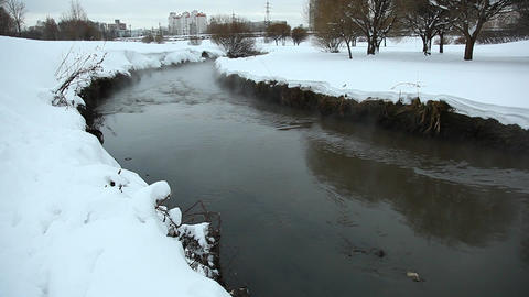 Shallow dirty channel run between snowy banks, vapour rise from gurgling water Live Action