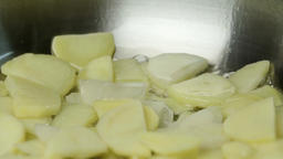 Sliced potatoes fried in a pan 4k сlose up video. Chopped chips on boiling oil Footage