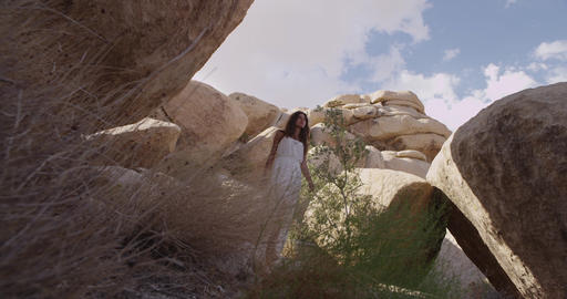 Girl walking in the desert through the rocks and caves. Mojave desert views. Slo Footage