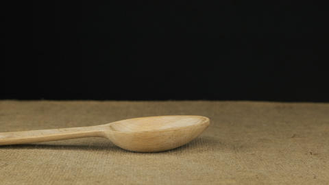 Grain buckwheat starts falling into the wooden spoon and fills it. Slow motion Live Action