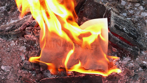 Word Minimarket on a white sheet of paper burns into a fire against. Slow motion Live Action