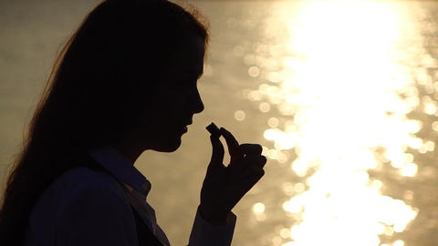 Woman take bite of candy, silhouetted half face portrait against shimmer water Live Action