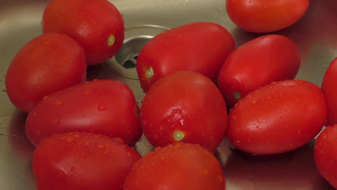 Female hands washing tomatoes at the kitchen sink Footage