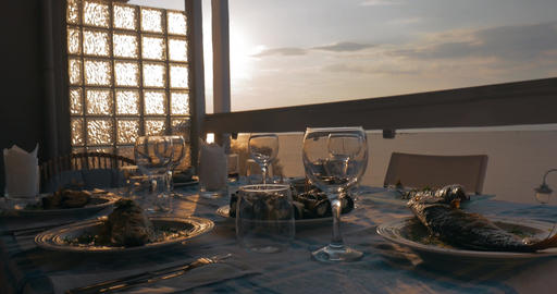 At sunset in city of Perea, Greece, dinner table served with cooked fish Footage