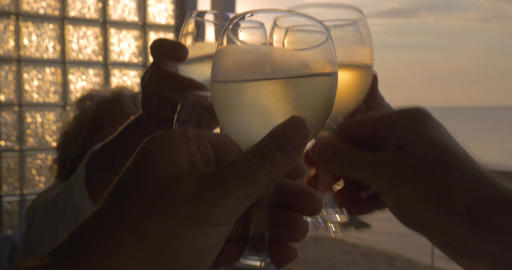 Family celebrates raising their glasses of white wine in city Perea, Greece ビデオ