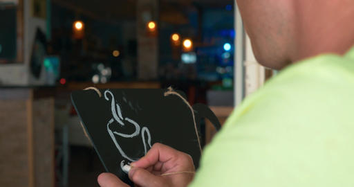 Man draws a chalk on a black board Footage