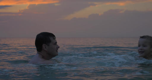At sunset father with son swimming in sea of city Perea, Greece Footage