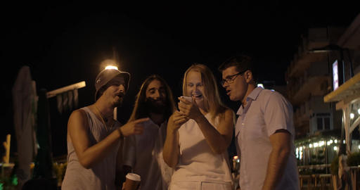 In evening in city of Perea, Greece young company taking selfies on a mobile pho Live Action