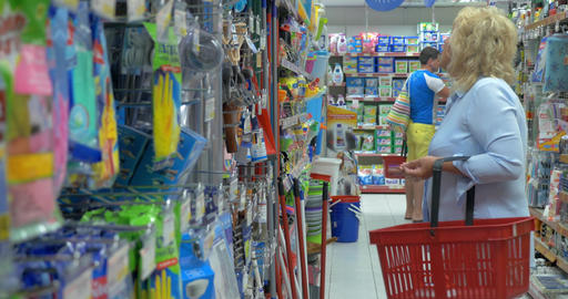 Senior woman is choosing household goods at supermarket with shop basket for cle Footage