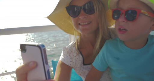 Young mother and her child are doing selfie on the boat. Little boy kisses mom o Footage